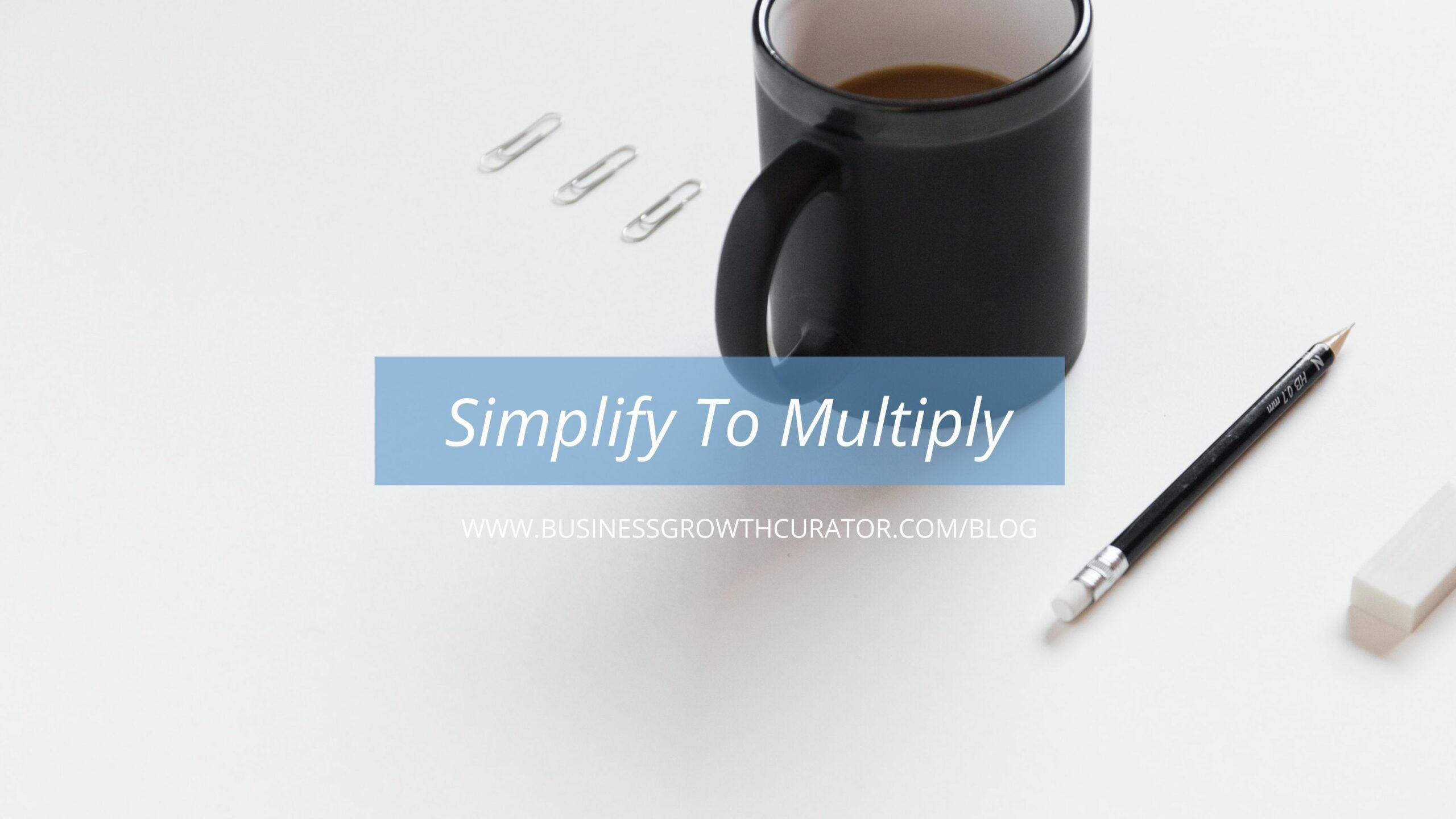 cup of coffee on white table with pen and paperclips lined up