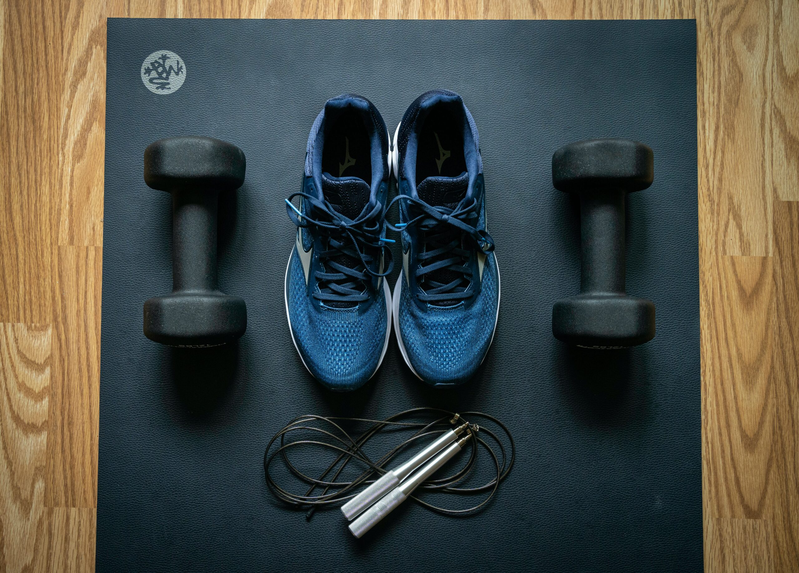 navy blue shoes, black weights, and jump rope on a black exercise matt
