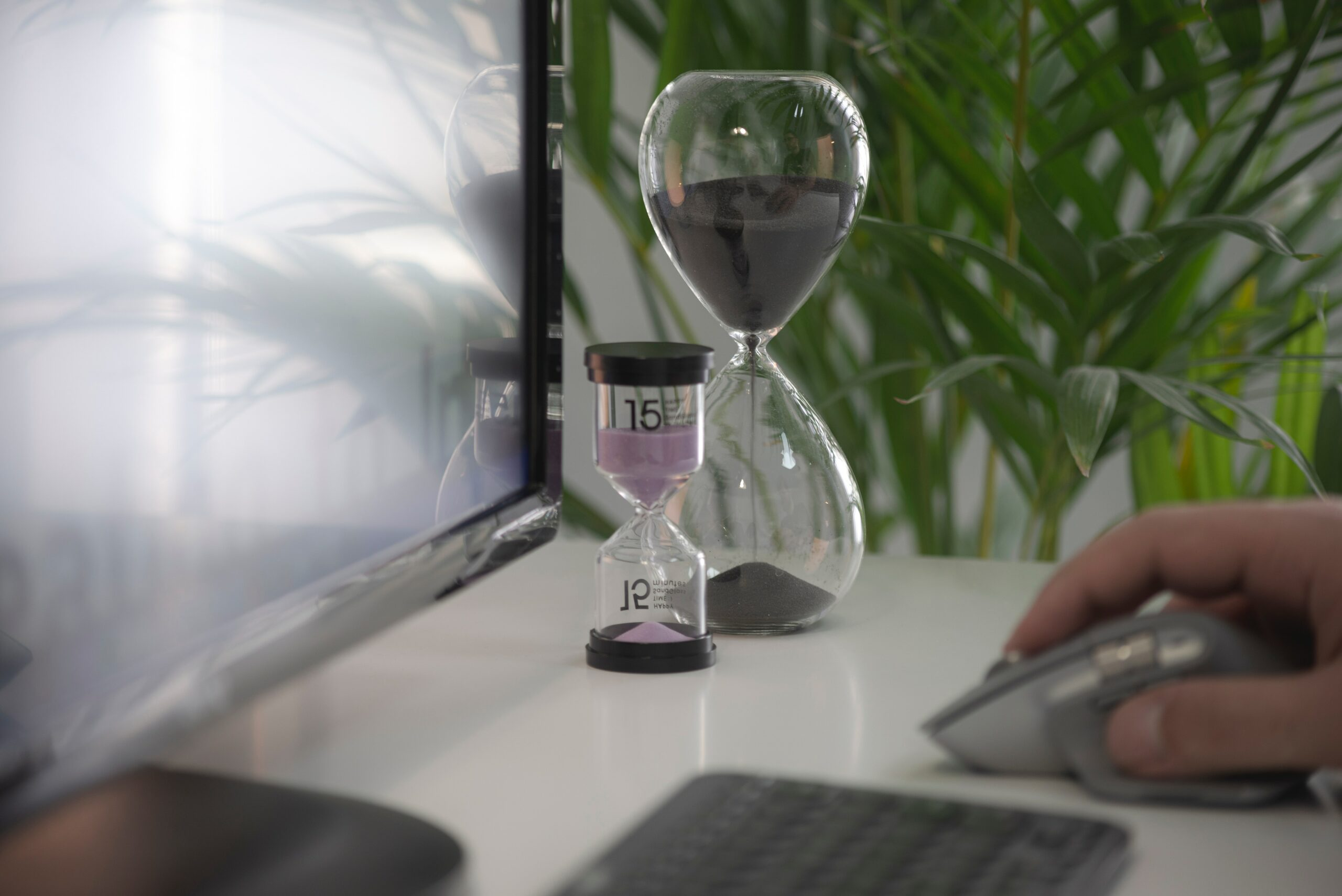 man working at computer with two hourglasses running