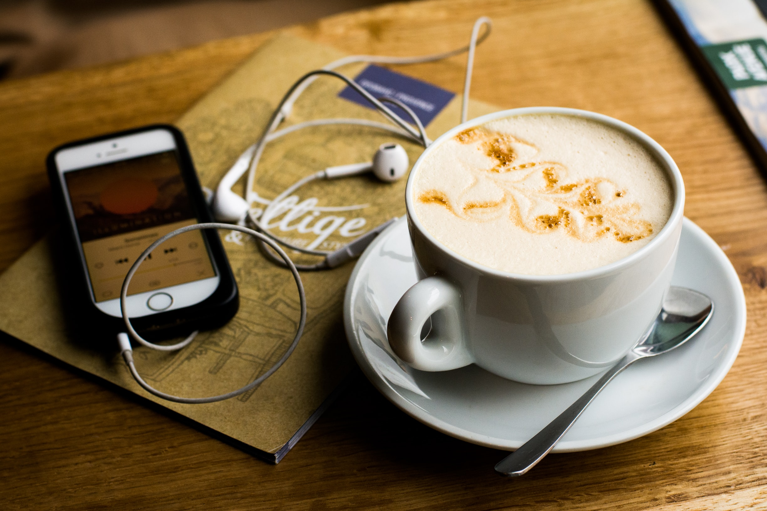 phone with media player and headphones, notebook, and latte on table