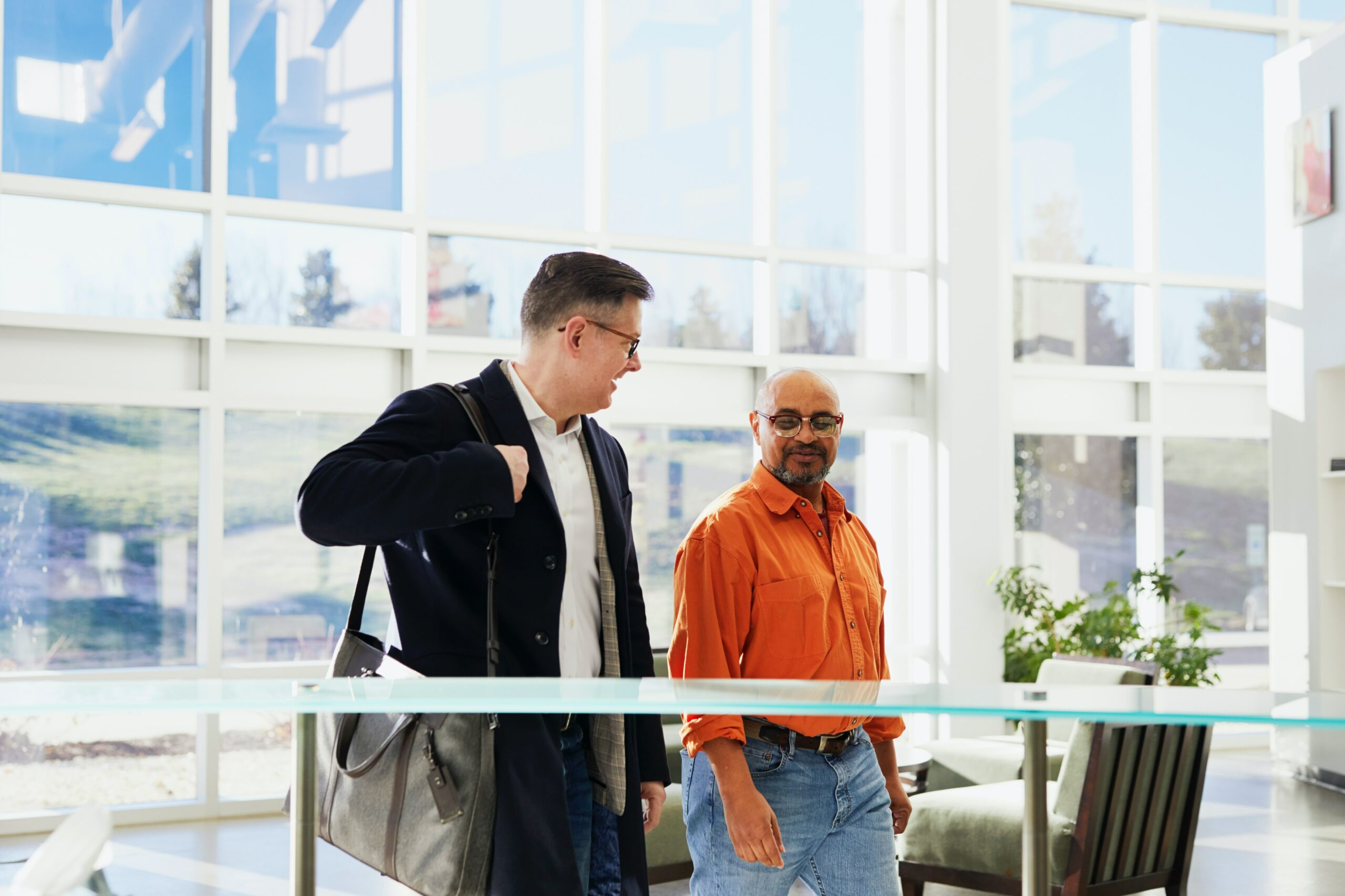 man in navy suit walking and talking to man in orange polo
