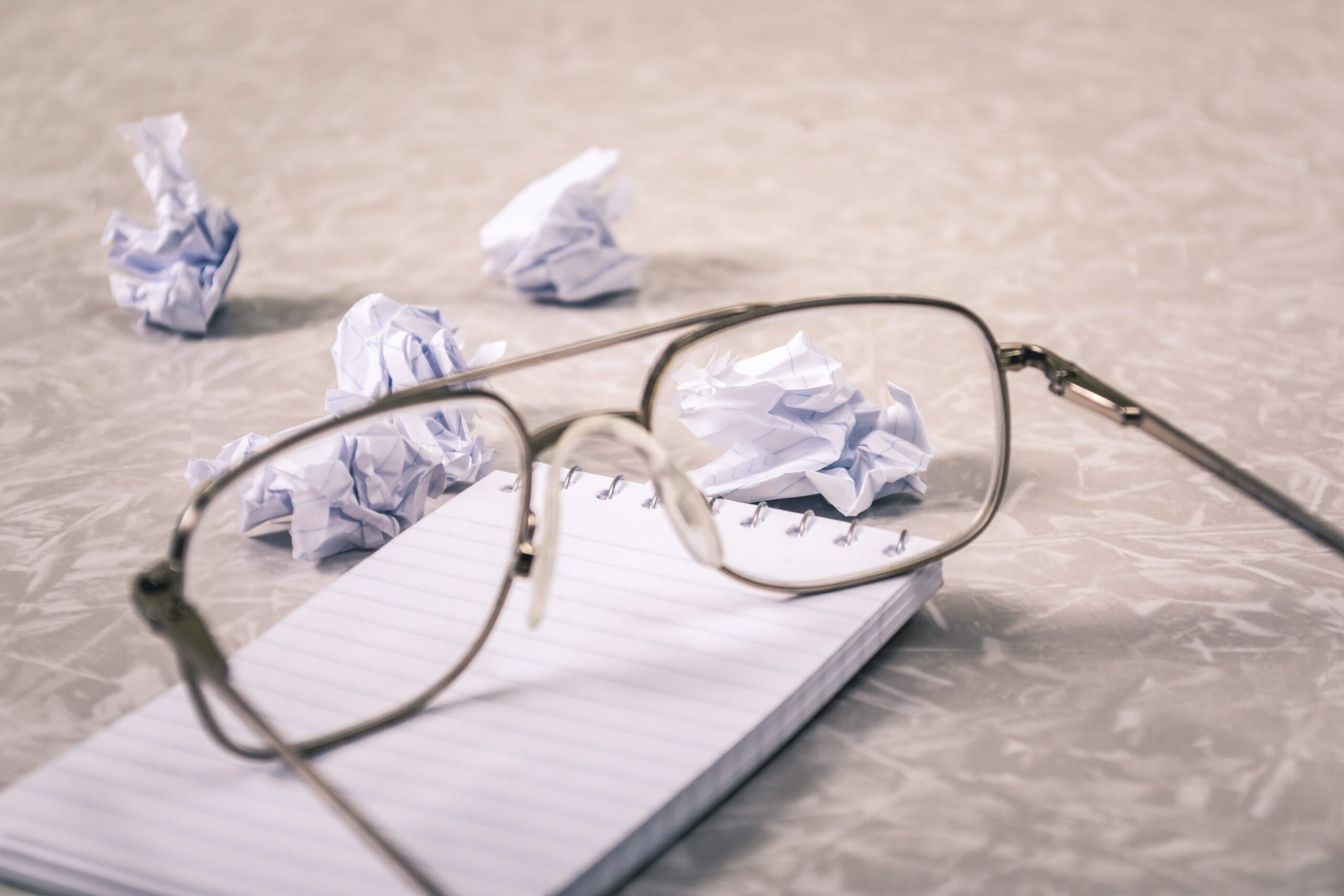 glasses sitting on top of white notepad with crumpled papers past them