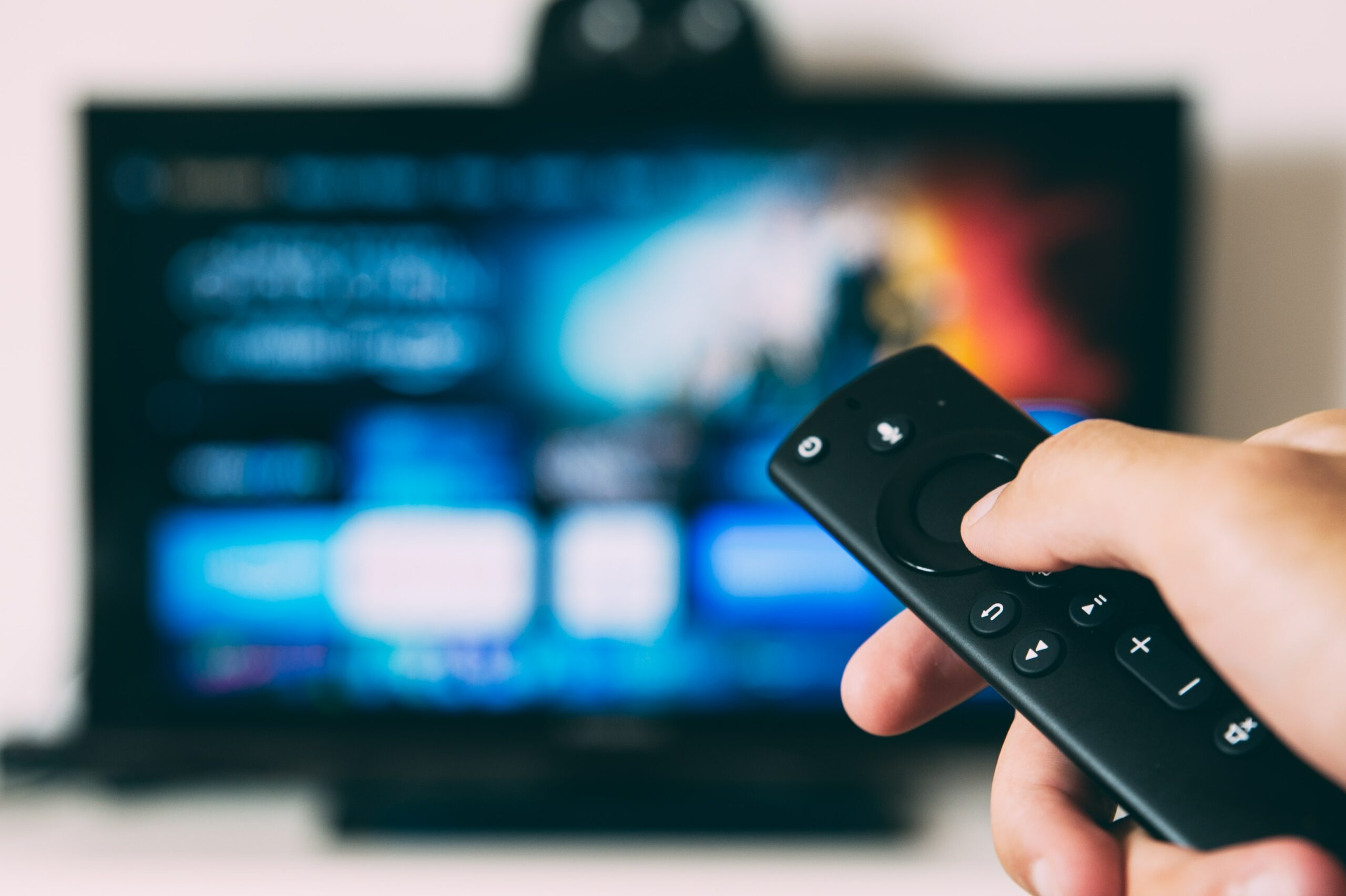 person holding apple tv remote with netflix home screen
