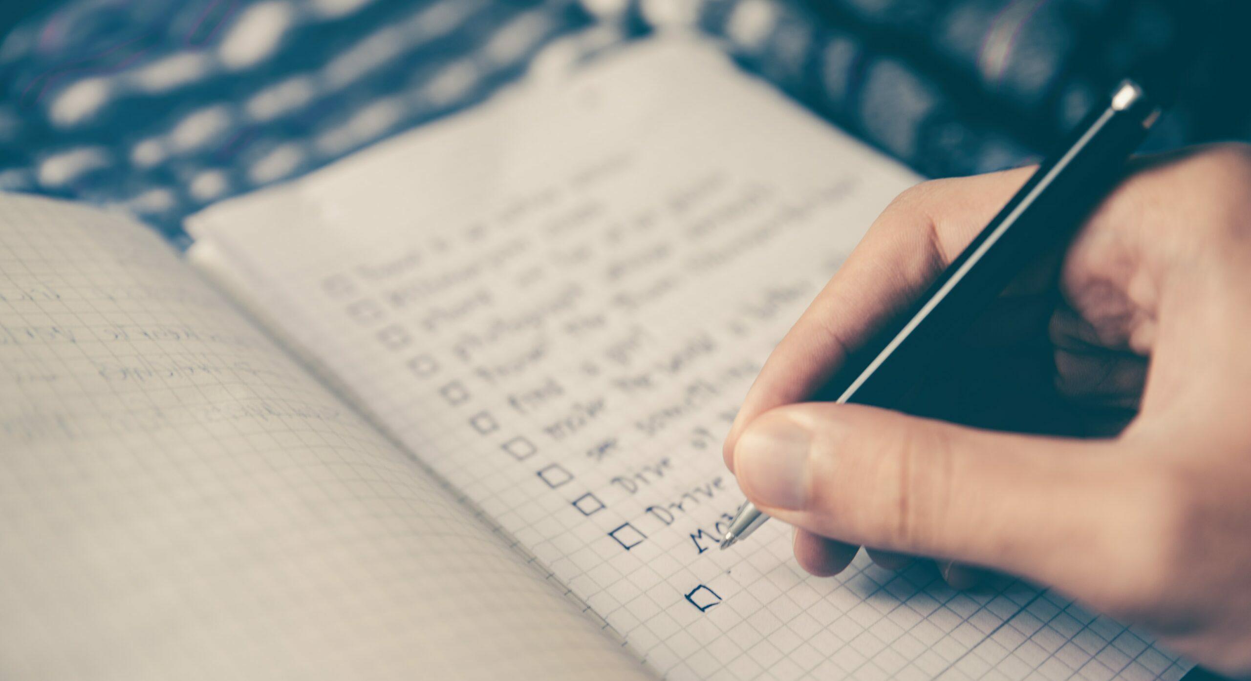 hand writing checklist in notebook